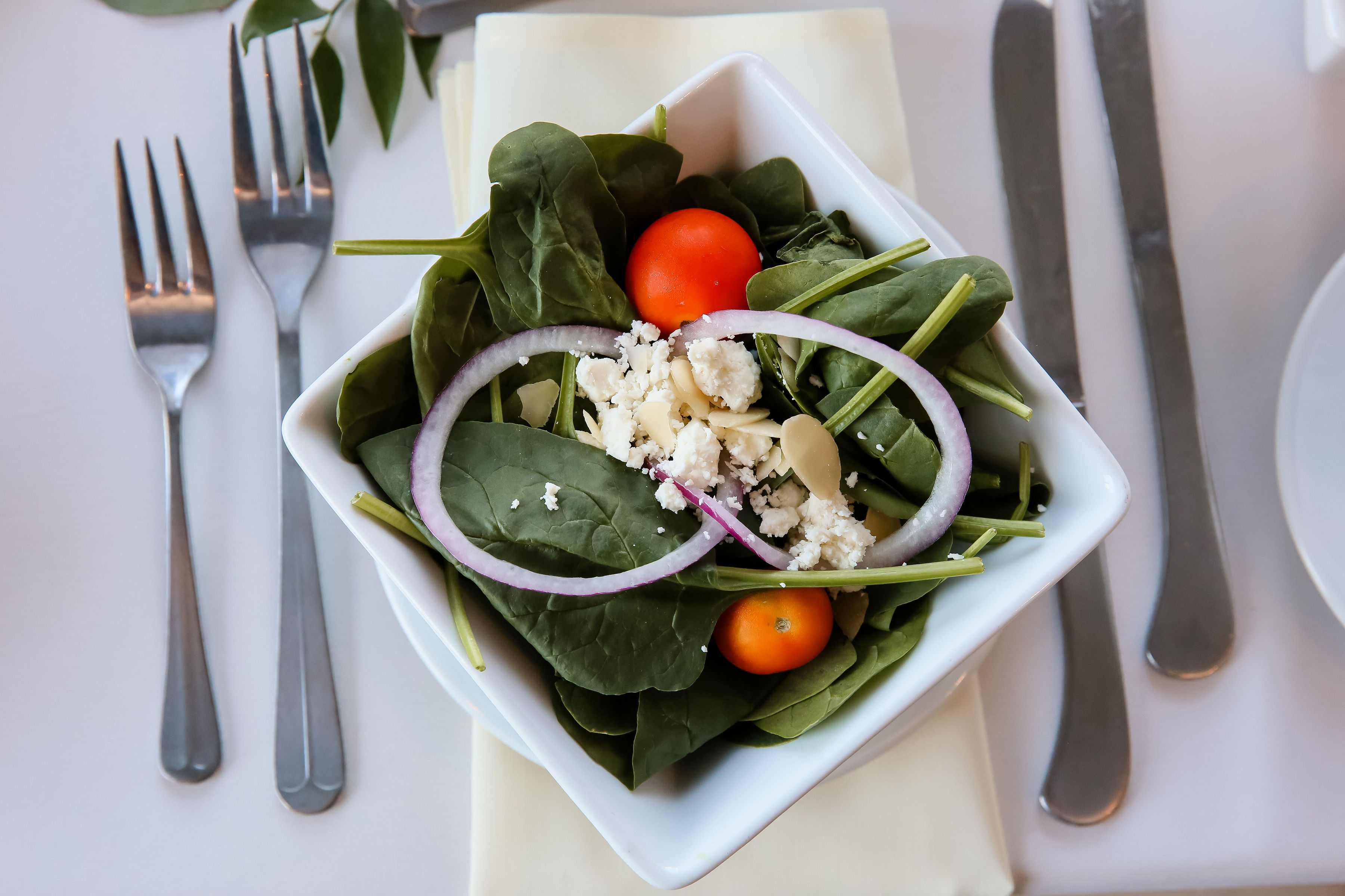 Spinach salad with goat cheese on a white set table.