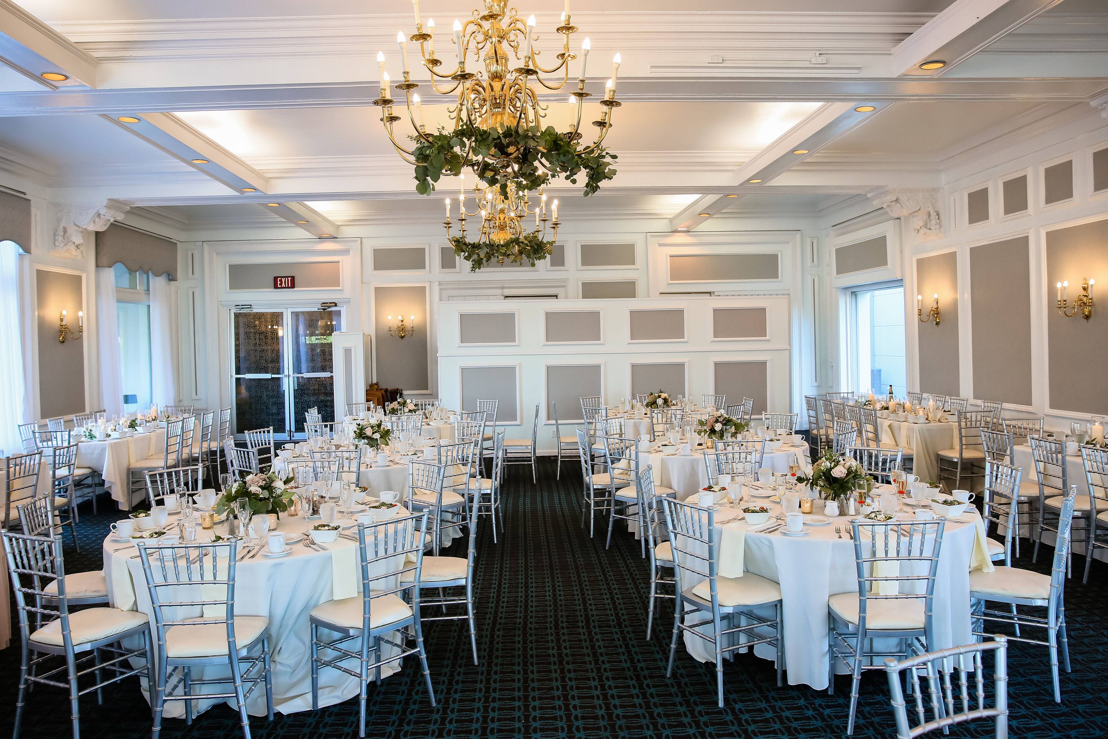 White Lion Room with gold chandeliers and Greenery. Round tables set with dining wear and flowers and white linens