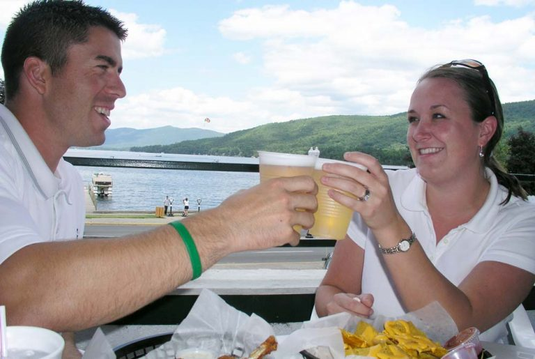 Couple dines at a Restaurant deck overlooking Lake George at The Fort William Henry Resort